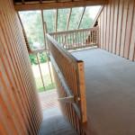 Chalupy k pronájmu na Šumavě - krytý prostor (veranda) slouží k posezení a odděluje zvukově i stavevně oba apartmány. Díky prosklené střeše nabízí výhled do údolí řeky Otavy.
